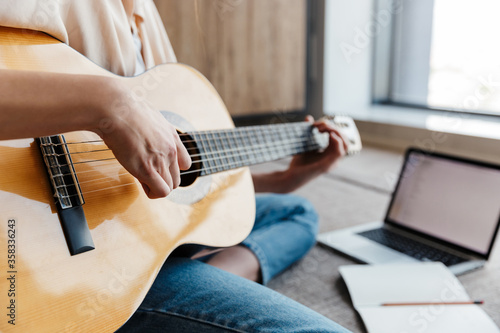 Image of young woman using laptop while playing acoustic guitar at home Canvas Print
