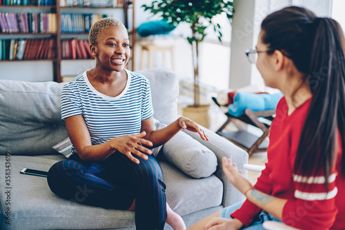 Fototapeta Cheerful african american woman talking with female friend spending time together at apartment, multiracial hipster girls having conversation at home interior, female explaining emotional gesture . obraz