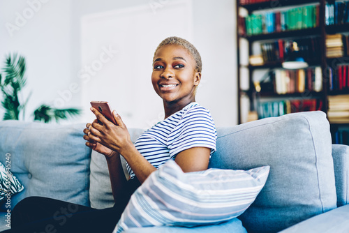 Fotografía Cheerful african american woman satisfied with wireless internet at home connecting smartphone for chatting and blogging,happy dark skinned hipster girl using mobile phone for sending message