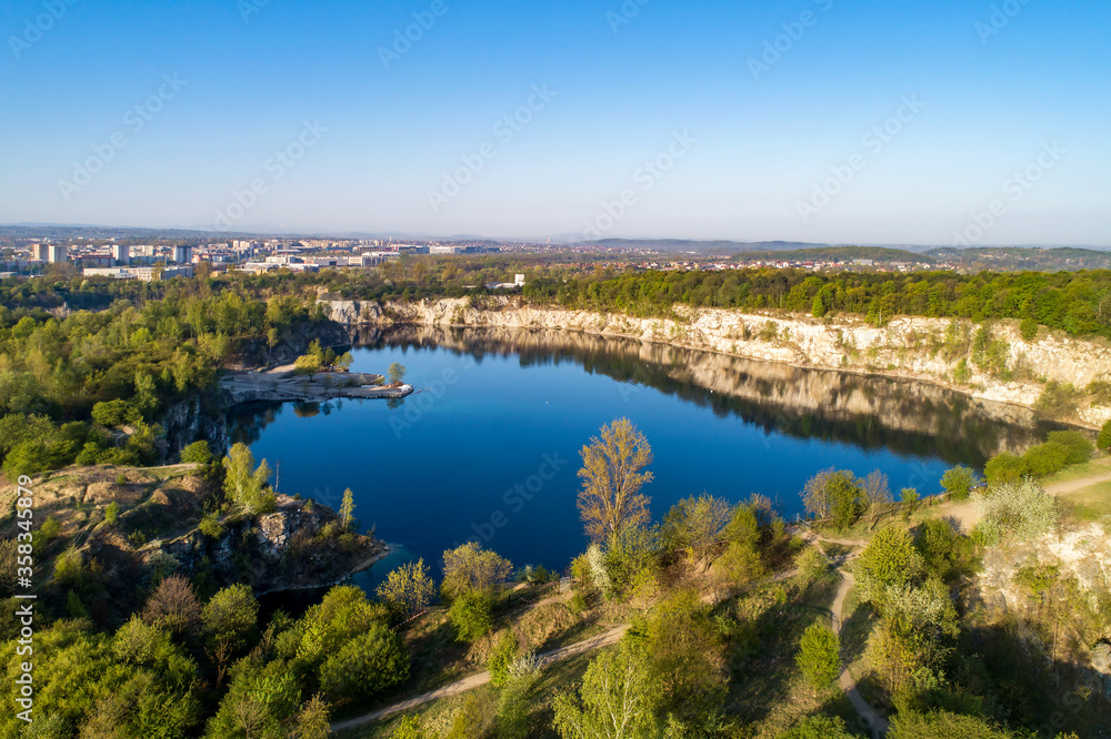 Krakow, Poland. Zakrzowek lake with steep cliffs in place of former flooded limestone quarry in Twardowski Rocks. Popular recreational place. Aerial view at sunrise