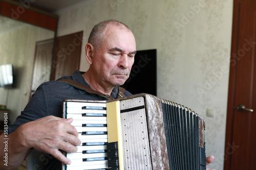 Serious man playing accordion Fototapet