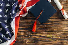 Top View Of Diploma And Graduation Cap Near American Flag With Stars And Stripes On Wooden Surface