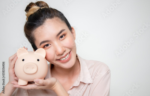 Fotografie, Tablou Asian women save money on pink pig-shaped savings in order to invest in the future and emergency episodes