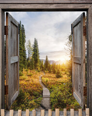 Antique wooden windows open to autumn wilderness at sunrise