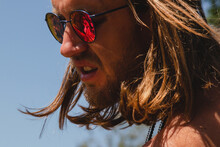 Outdoor Portrait Of Sexy Shirtless Long-haired Young Man In Red Sunglasses. Horizontal Image.