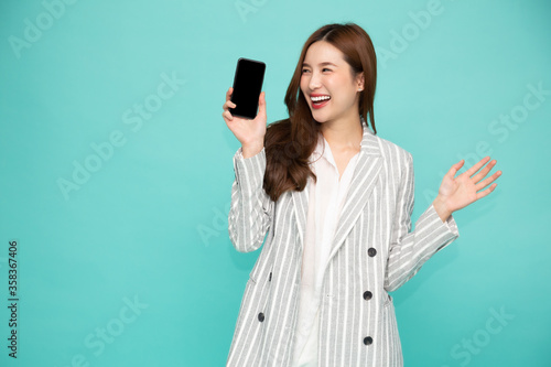 Fotomural Happy asian woman smile and holding mobile phone isolated over light green backg