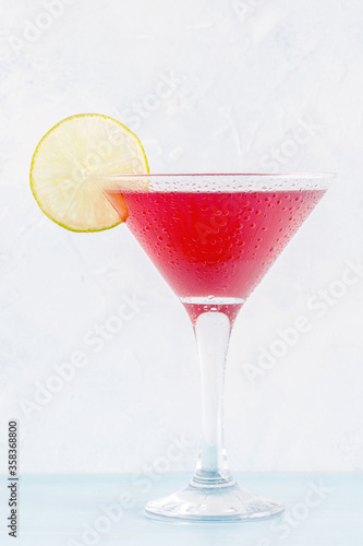 Fotografiet Glass of cosmopolitan cocktail decorated with lime