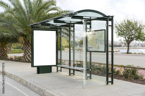 Fototapeta Blank white, vertical mockup of bus stop billboard in empty Caddebostan street