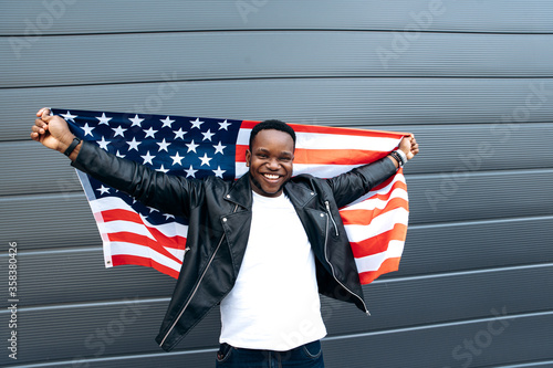 Fotografija Cheerful attractive african american guy stands with hands up holds flag of USA