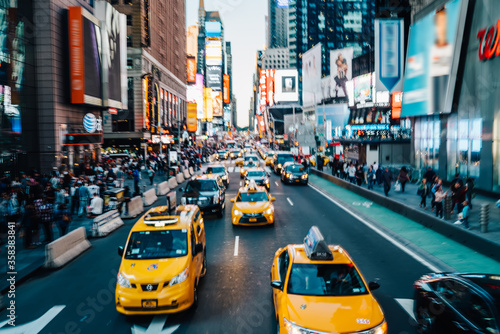 Fototapeta Motion blur effect,Times square with illuminated buildings and advertise on front crowded streets and yellow cabs for transportation tourists,midtown in New York with busy traffic and taxi cars moving obraz