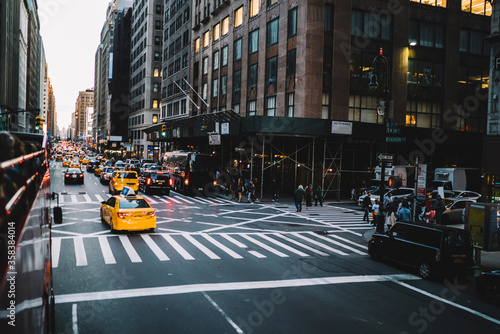 Fotografie, Tablou Traffic on avenue roads in midtown with yellow taxi and cars rushing in jam, Man