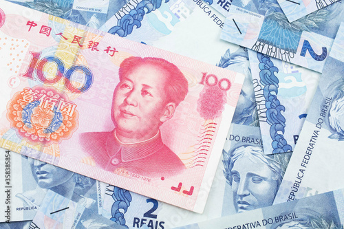 A close up image of a red, one hundred Chinese yuan bank note, close up on a background of Brazilian two reais bank notes Canvas-taulu