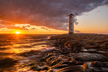 lighthouse in the shape of a windmill in Swinoujscie in Poland during the dramatic sunset.