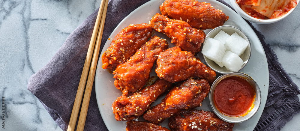 Fototapeta korean fried chicken wings in gochujang sauce with pickled radish and kimchi wide composition