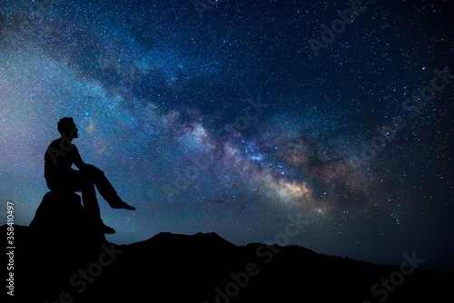Photo Man sitting outdoors admiring the sky full of stars