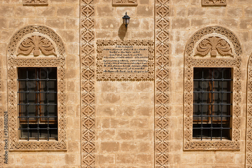 Photo Intricate carvings and a plaque with Aramaic script decorate the stone facade an