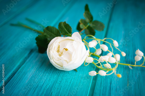 Romantic white bouquet with rose tree and lilly of the valley flowers, teal wooden background.