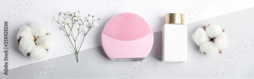 Flat lay composition with face cleansing brush on color background, banner design. Cosmetic accessory