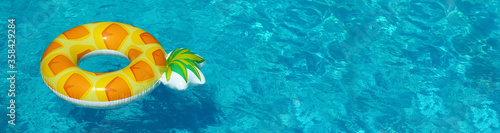 Fototapeta Bright inflatable pineapple ring floating in swimming pool on sunny day, space for text. Banner design obraz