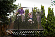 Father And Daughter Jumping On...