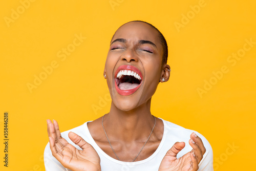 Close up portrait of happy young African American woman laughing out loud with both hands in clapping gesture isolated studio yellow background