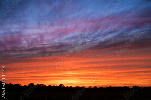 Vibrant Evening Sky - A sunset paints a cloudy sky with vibrant colors over silhouetted trees on the horizon in rural America.