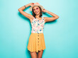 Young beautiful woman looking at camera in hat.Trendy girl in casual summer white T-shirt and yellow skirt in round sunglasses. Positive female shows facial emotions. Funny model isolated on blue