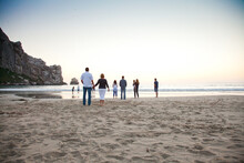 Multi-generational Family Standing On The Beach. Family Looking Out Toward The Water.