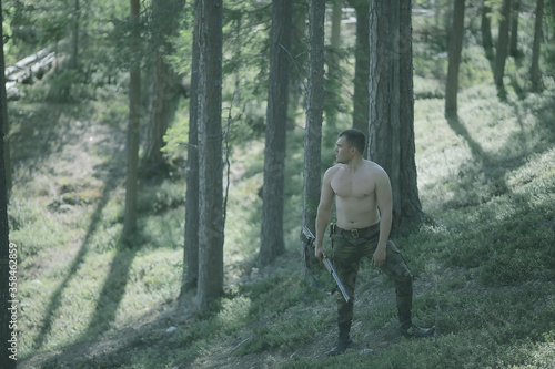 Photo man goes hunting forest summer / landscape in the forest, huntsman with a huntin