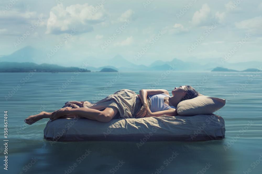 Fototapeta Sleeping woman lies on mattress in a water.