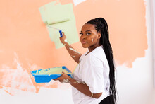 Young Happy African American Woman Painting Interior Wall With Paint Roller In New House. A Woman With Roller Applying Paint On A Wall.