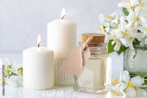 Spa composition with jasmine flowers on a white table close-up. Canvas Print