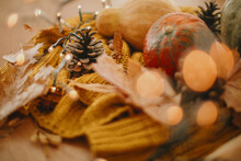 Autumn Hygge. Cozy Moody Image Of Pumpkin, Autumn Leaves,  Warm Lights And Pine Cone On Yellow Knitted Sweater. Selective Focus And Yellow Bokeh