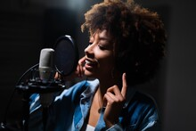 Close Up Of An Young Professional Smiling Energetic African Female Singer Wearing Headphones Is Performing A New Song With A Microphone While Recording It In A Music Studio.