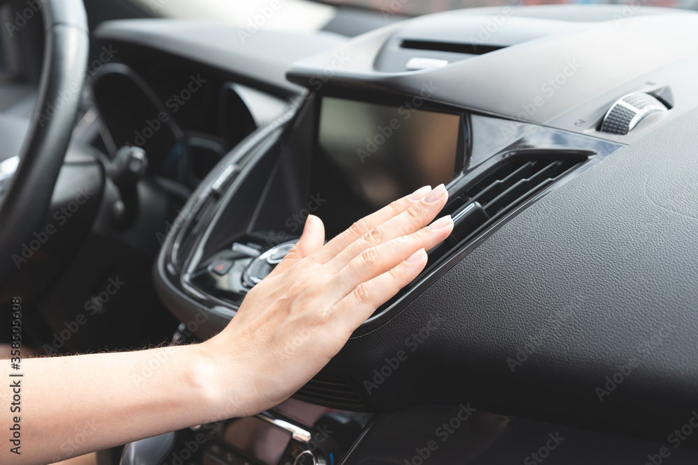 Fototapeta Woman checks air conditioning in a car