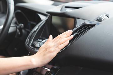 Woman checks air conditioning in a car