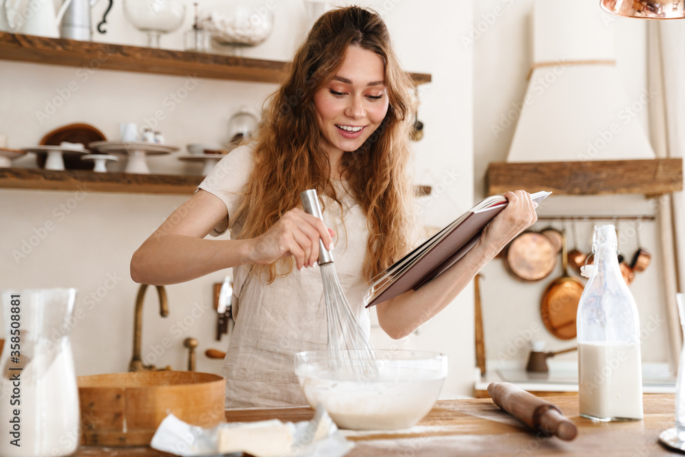 Fototapeta Attractive young cheerful girl baking at the kitchen