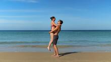 Joyful Young Couple Hugs On Su...