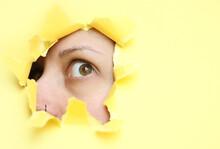 A Woman Looks Through A Hole I...