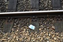 Gesichtsmaske Als Müll, Mundnasenschutz Für Corona Als Umweltverschmutzung, Mundschutz Gegen Covid-19 Als Abfall Auf Bahngeleisen