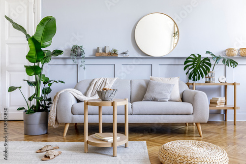 Stylish living room interior with design grey sofa, coffe table, rattan pouf, basket, shelf, mirror, tropical plants, decoration, carpet and elegant personal accessories in modern home decor.