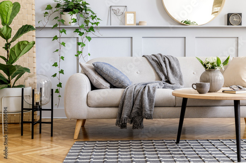 Obraz na plátně Scandinavian concept of living room interior with design sofa, coffee table, plant in pot, flowers, carpet, plaid, pillow, shelf, decoration and personal accessories in modern home staging