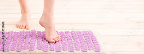 Photo Female feet on acupressure mat