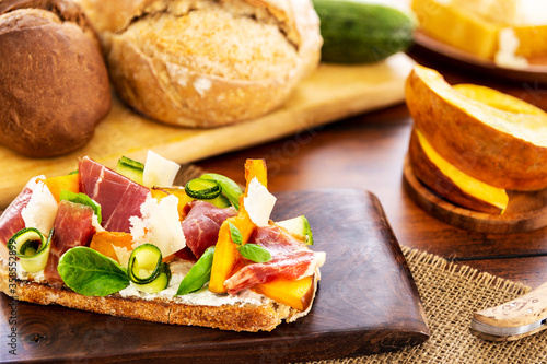 Open faced sandwich with iberico ham, parmesan and goat cheese, zucchini, pumpkin, basil and chives on sourdough bread Canvas Print