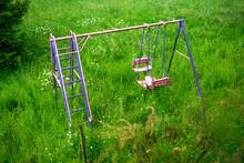 Colorful Swing In Garden Overgrown By Field Of Flowers