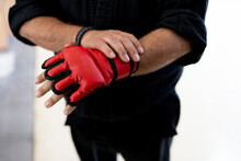 Crop Anonymous Male Mixed Martial Arts Fighter Wearing Red Boxing Glove While Preparing For Training