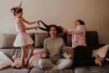 Excited Little Girl And Teen Boy Pulling Hair Of Adult Woman Sitting In Lotus Pose On Bed And Meditating