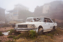 Vehicle With Shattered Windshield Located On Junkyard On Misty Day On Street Of Grungy Town