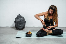 Calm Female In Active Wear Taking Off Wooden Beads While Sitting On Yoga Mat In Padmasana In Room With Buddha Head And Singing Bowl