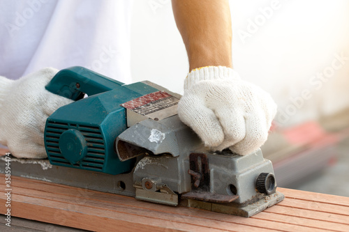 Carpenter man use electric planers for scrub wood Canvas Print